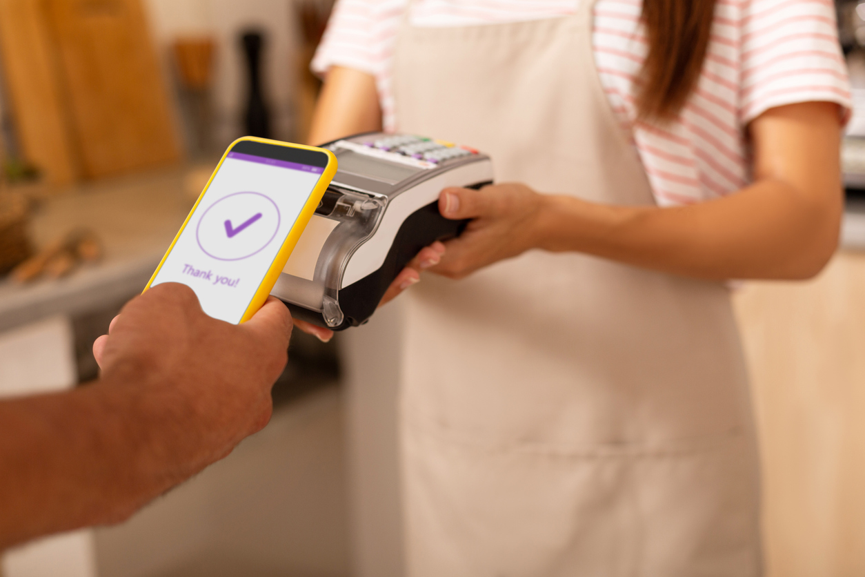 Close up of man processing contactless payment in cafeteria